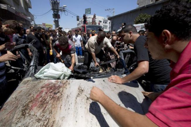 People gather around a vehicle targeted in an Israeli airstrike on Gaza City on July 8, 2014 that killed four Palestinians. (Photo: AFP - Mohammed Abed) http://english.al-akhbar.com/content/israeli-war-jets-bomb-50-sites-gaza