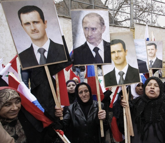 FILE - In this Sunday, March 4, 2012 file photo, Syrians hold posters of Syrian President Bashar Assad, far left, and Russian President Vladimir Putin, second left, during a pro-Syrian goverment protest in front of the Russian Embassy in Damascus, Syria. In ramping up its military involvement in Syria's civil war, Russia appears to be betting that the West, horrified by Islamic State's atrocities, may be willing to tolerate Assad for a while, perhaps as part of a transition. (AP Photo/Muzaffar Salman, File)